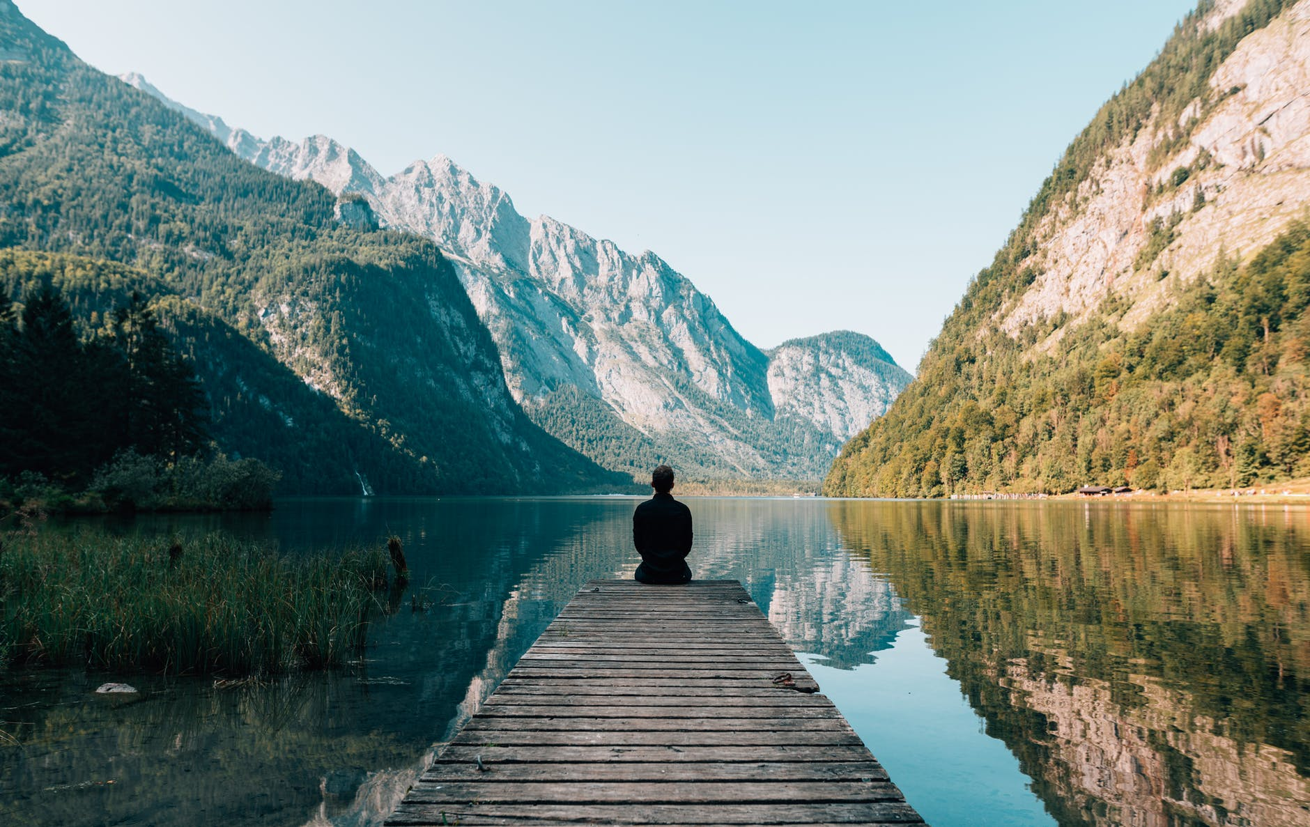 a person sitting on wooden planks across the lake scenery
