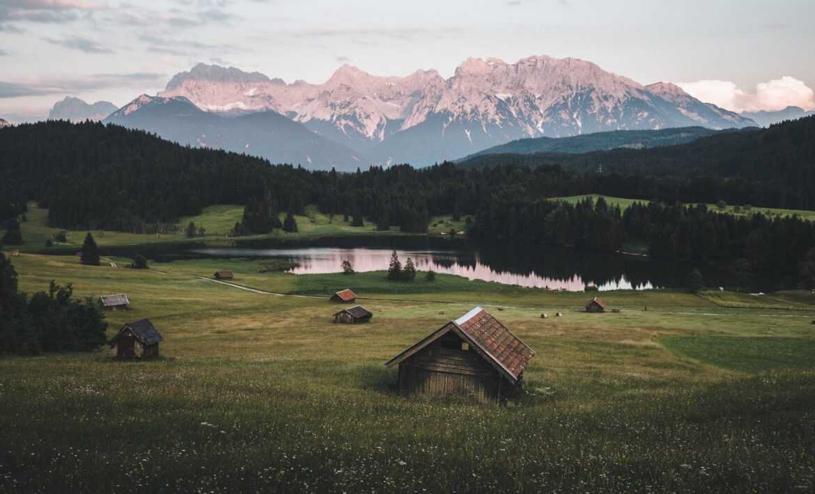 brown wooden house on green grass field near green trees and mountains